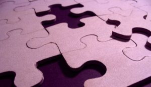 A purple puzzle with missing pieces