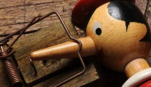 A wooden doll with a long nose stuck in a mouse trap