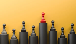 Red pawn of chess, standing out from the crowd of black pawns