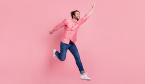 Person jumping having fun success isolated over pink pastel color background