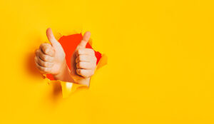 Two hands show OK gesture, approval, liking, acceptance through torn hole in yellow paper wall.
