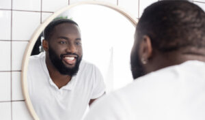 A picture of a smiling person looking into a mirror
