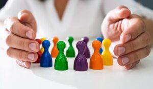 A picture of hands possessively guarding a series of coloured pawns