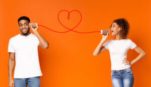 Two people with a can phone on an orange background