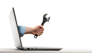 The human hand with black wrench stick out of a laptop screen