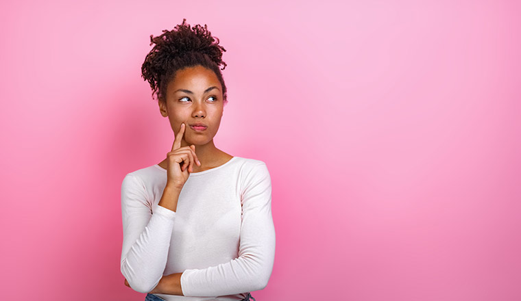 A person in a thinking pose on a pink background