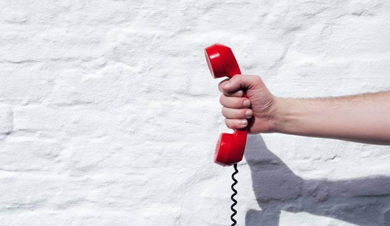 Shot of a landline telephone receiver being held