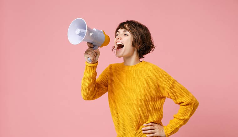 Person on megaphone in front of pink background
