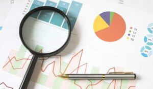 A magnifying glass an pen on business charts