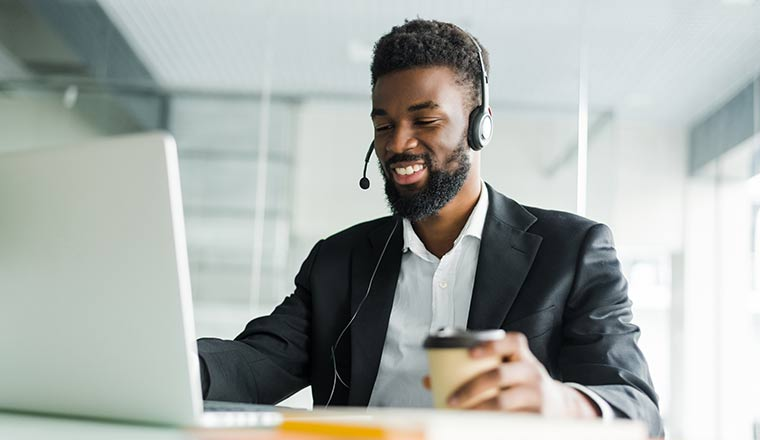 A customer support operator with hands-free headset working in the office.