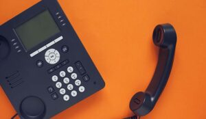 An office phone isolated on an orange background