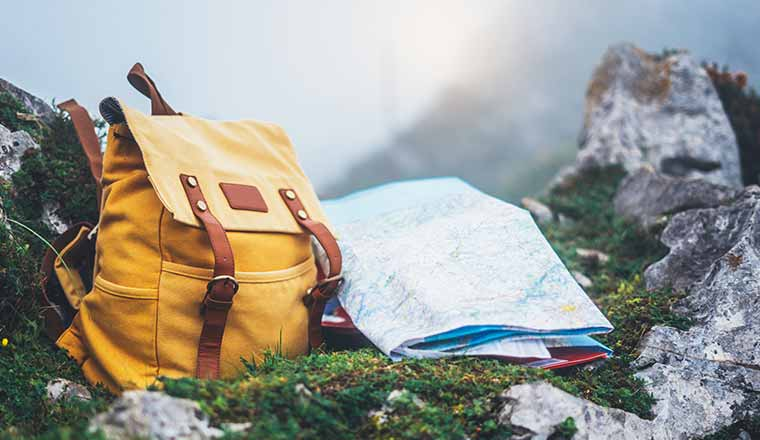 A yellow backpack and map on mountain background