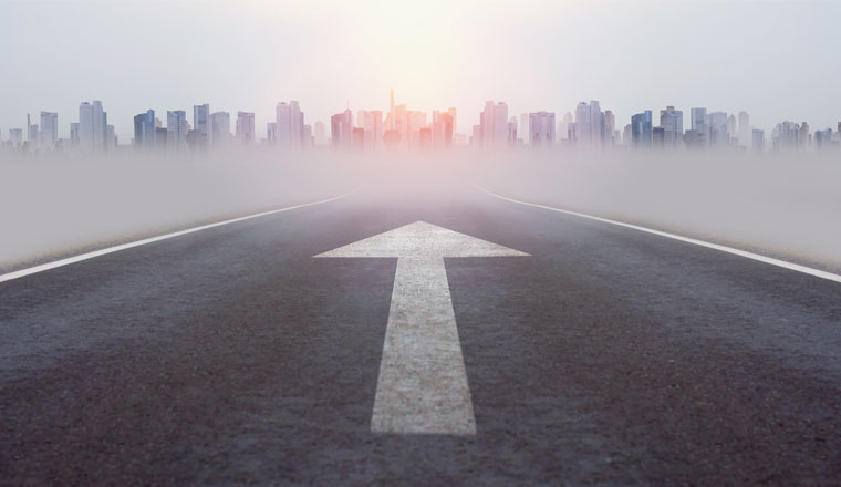 A picture of a road heading into a city with a white arrow on the tarmac