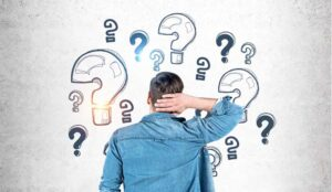 A rear view picture of a person scratching their head looking at question marks