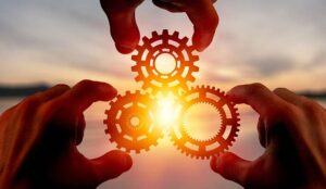 Hands holding cogs with a sunset in the background