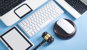 Judge gavel with a computer mouse, keyboard, tablet, laptop.
