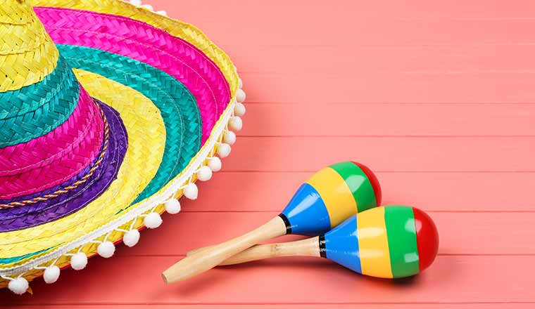 Mexican hat and maracas on wooden table