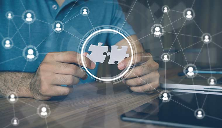 Person holding pieces of jigsaw puzzle with networked people icons