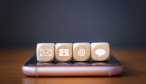 Close-up of a phone, email, chat and post icons wooden dice arranging in a row on mobile phone