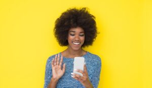 Person on phone isolated on yellow background