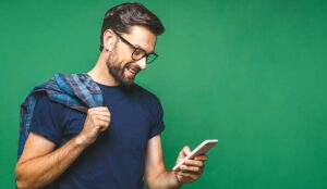 Smiling person holding smart phone and looking at it