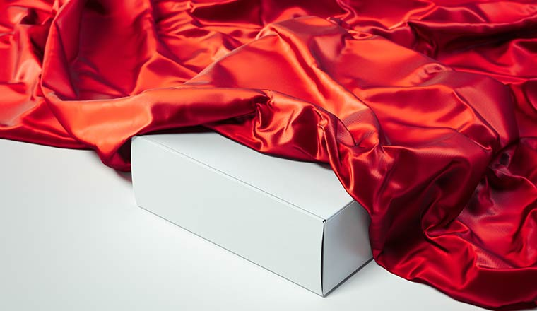 Close up of white blank box under red cloth being unveiled on white background