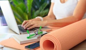 Person on a laptop in the background with exercise mat in foregraound