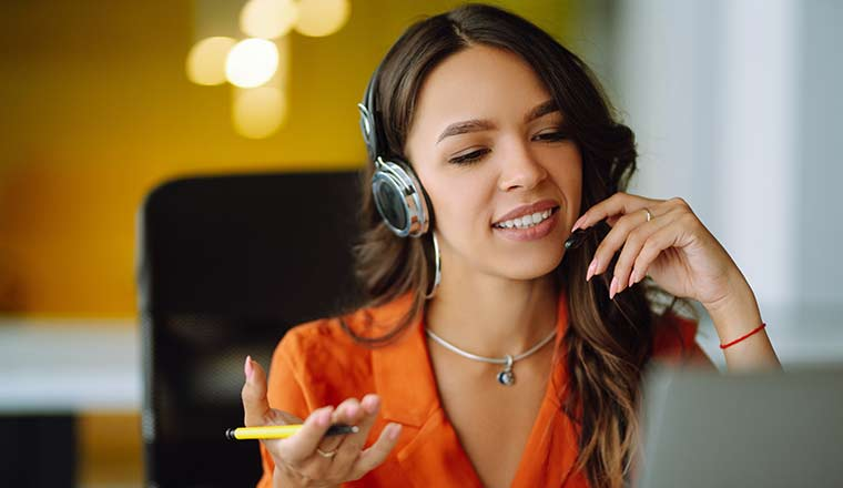 Happy agent with headsets working in a call centre.