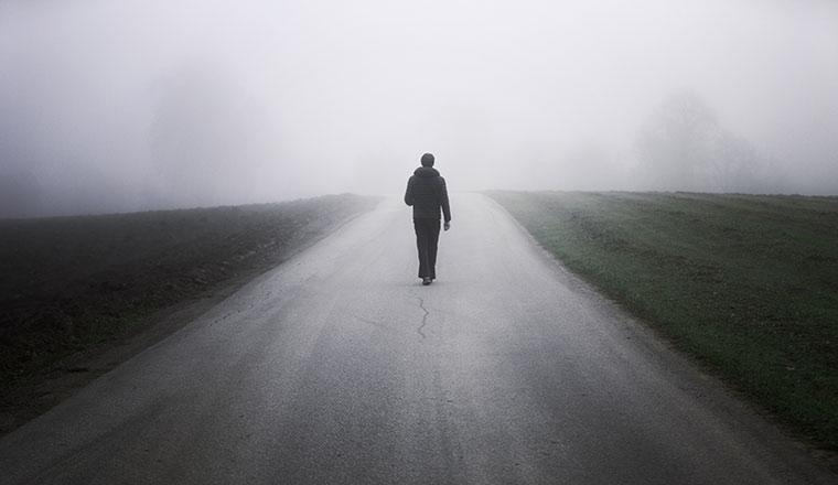 Person walking alone on rural misty asphalt road