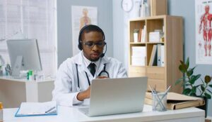 A physician in white coat speaking on video call in headset on laptop