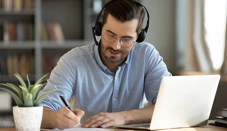 Person sitting at a desk with headset learning