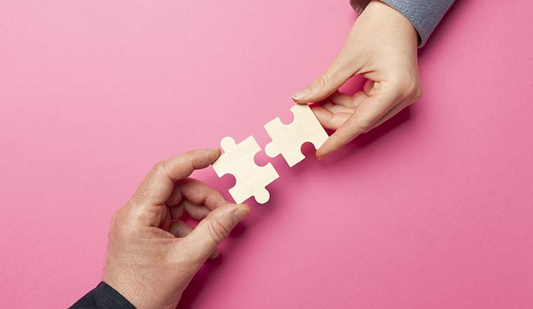 Two hands connect puzzles on a pink background.