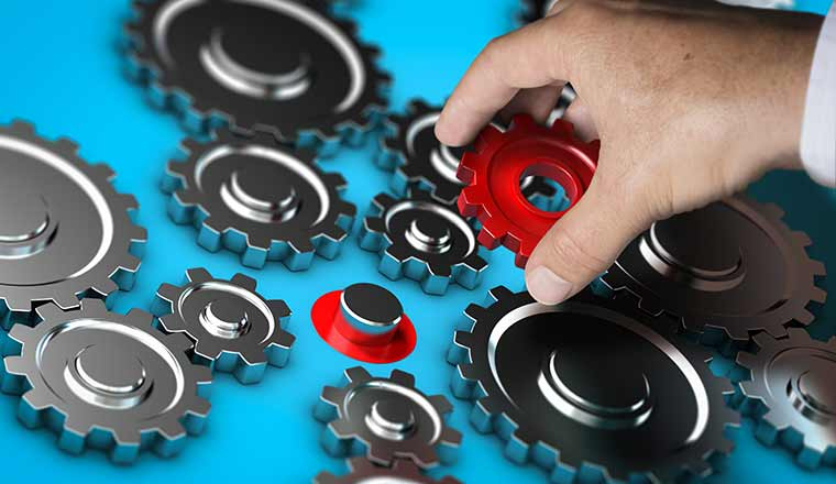 A red cog being placed among other cogs acting as the keystone