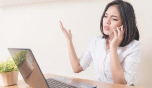 Frustrated person on phone in front of laptop