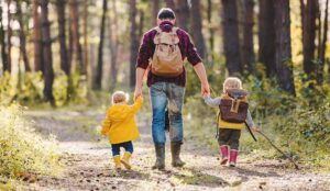 An adult walking in the woods with two children