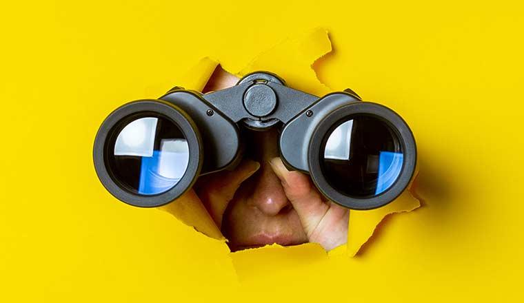 hand holds black binoculars on a yellow background
