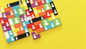 Interlocked puzzle blocks with people icons over yellow background