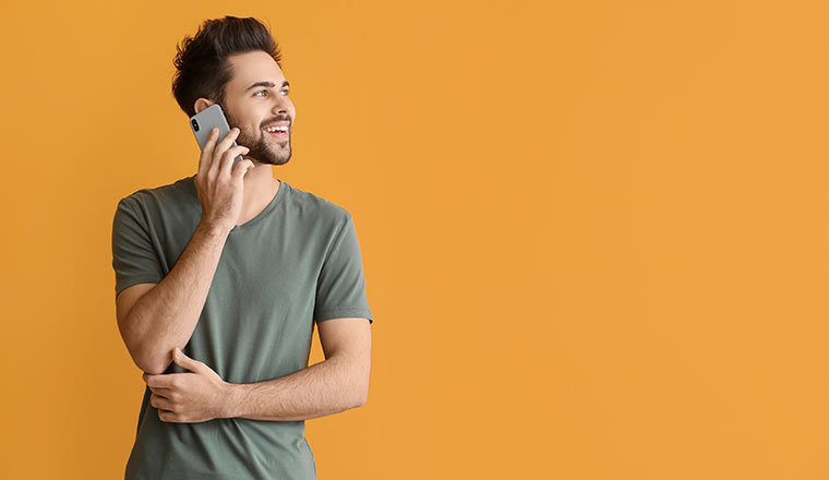 Person talking on mobile phone on color background