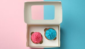 Box with two different cupcakes on color background