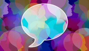 Colourful face silhouettes behind a partially transparent speech bubble