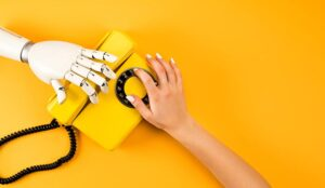 A human hand and robot hand reaching for vintage phone on yellow background