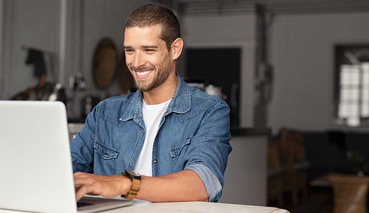 A happy person working on a laptop