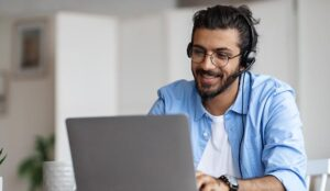 Person In Headset Working With Laptop