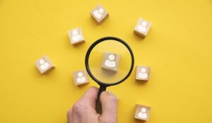 Magnifying glass over wooden blocks with people