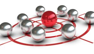 A red ball in the centre of a target surrounded by grey balls