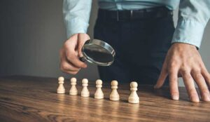 A magnifying glass evaluating six chess pieces