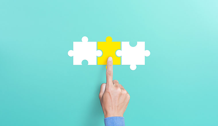 Mergers and acquisition concept with puzzle pieces on blue background