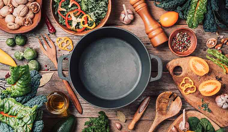 Various ingredients and empty iron cooking pot, wooden bowls, spoons on wooden background.