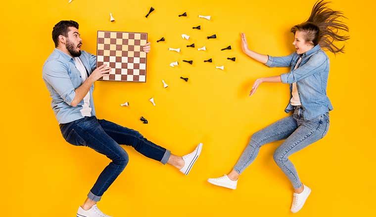 Two people jumping with a chess board representing important skills